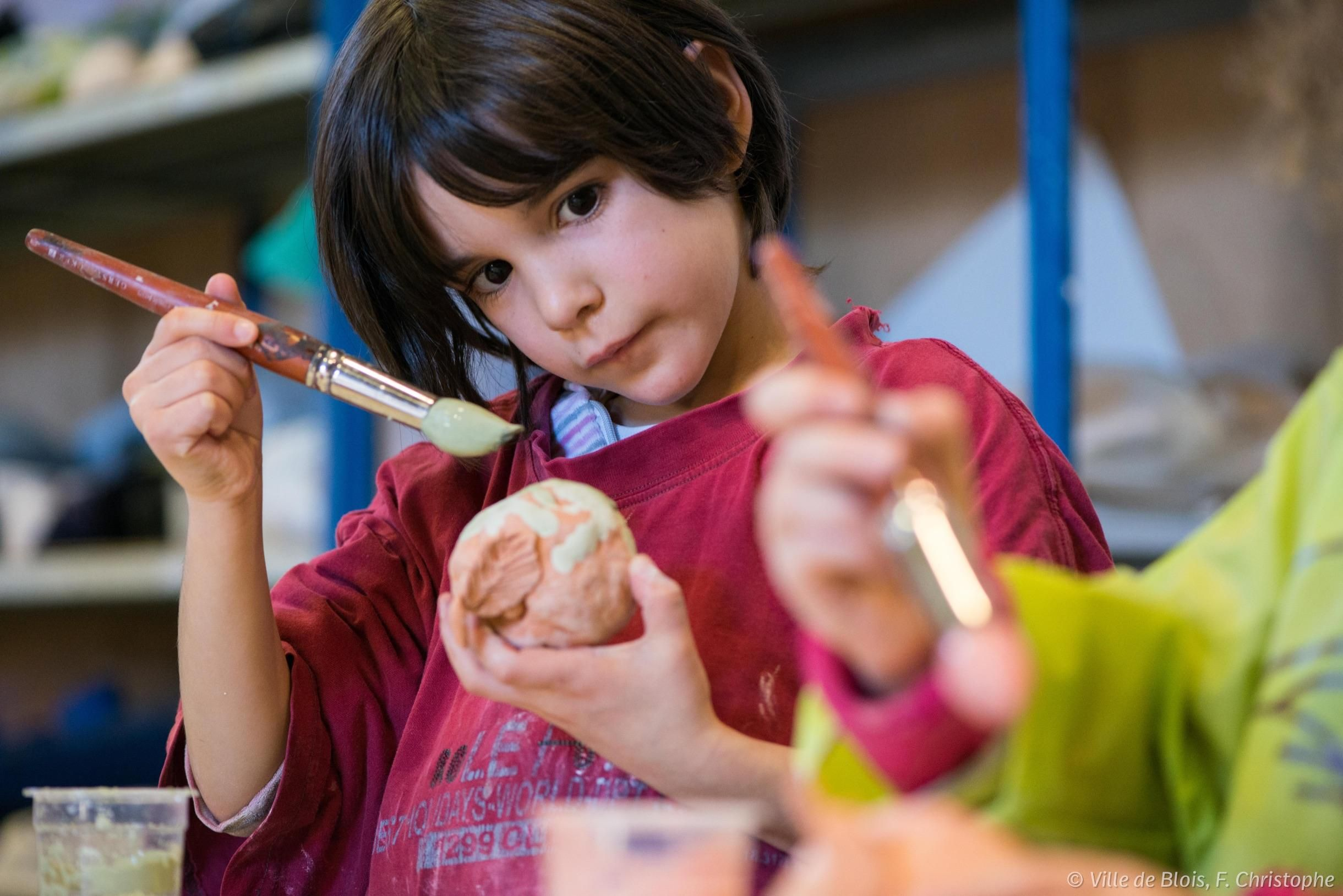 Une petite fille fait de la peinture sur objet.