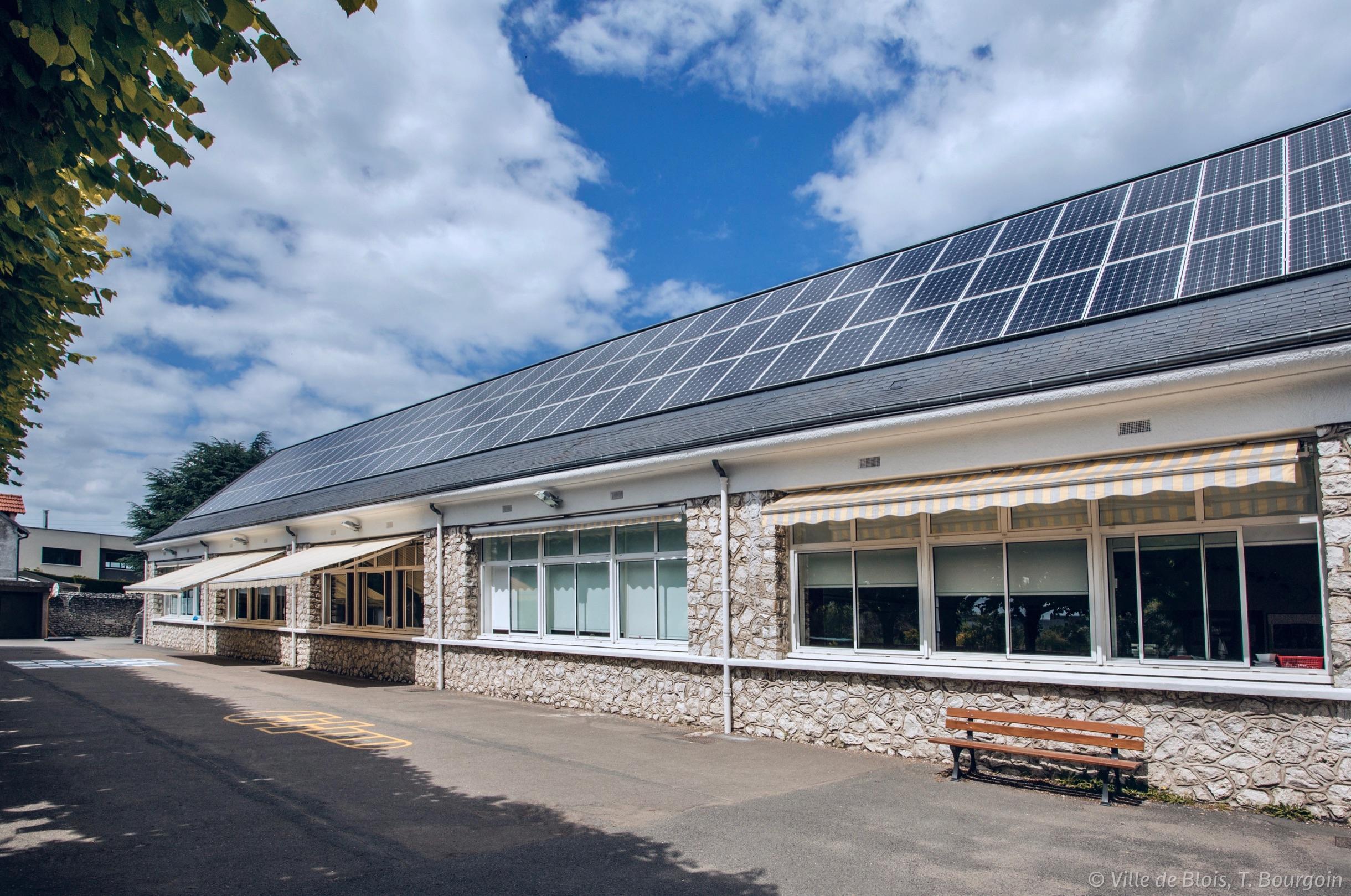 Cour de l'école Raphaël-Perié, avec des panneaux solaires sur le toit du bâtiment.