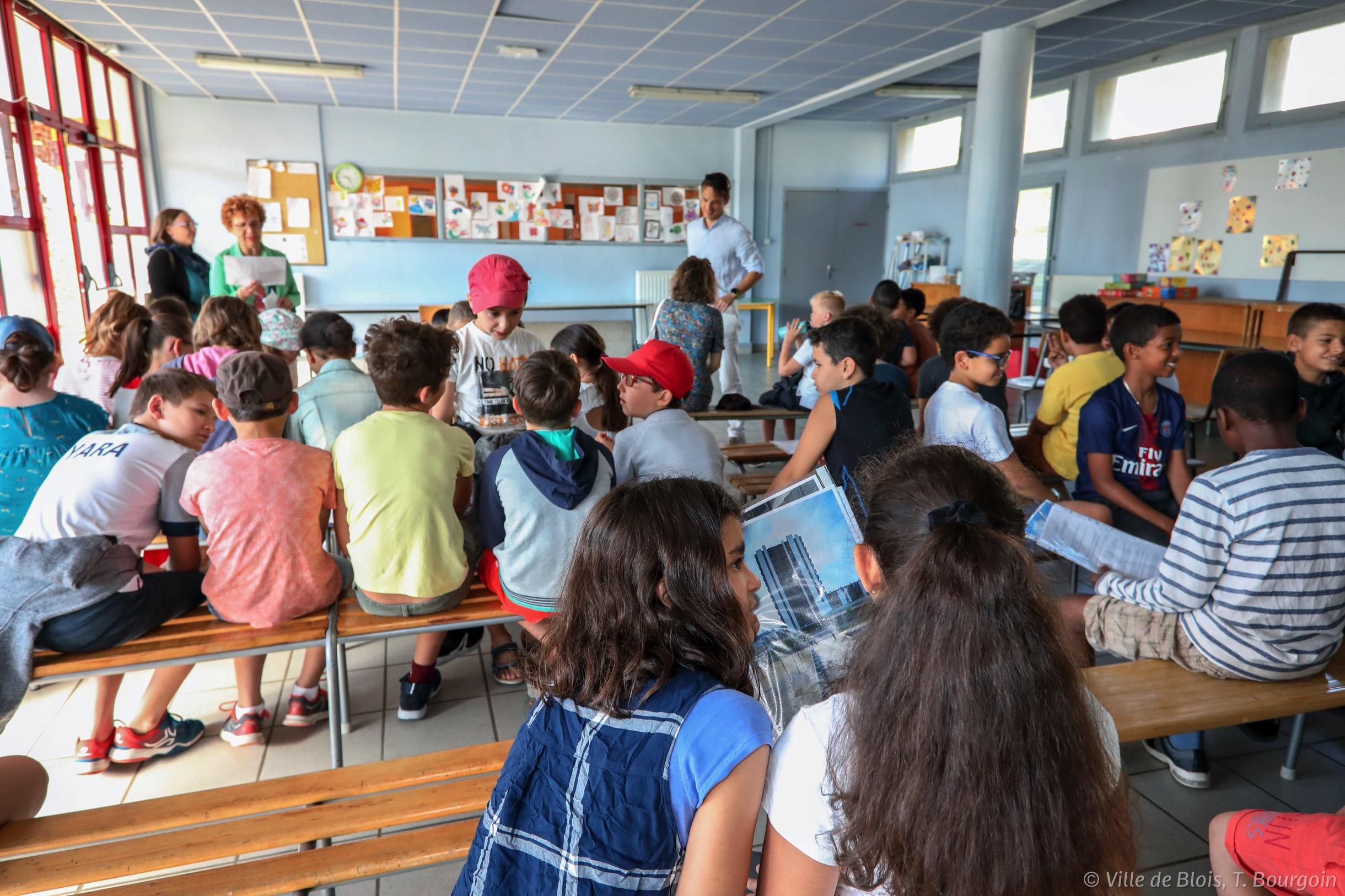 Des enfants rassemblés dans une classe échangent entre eux.