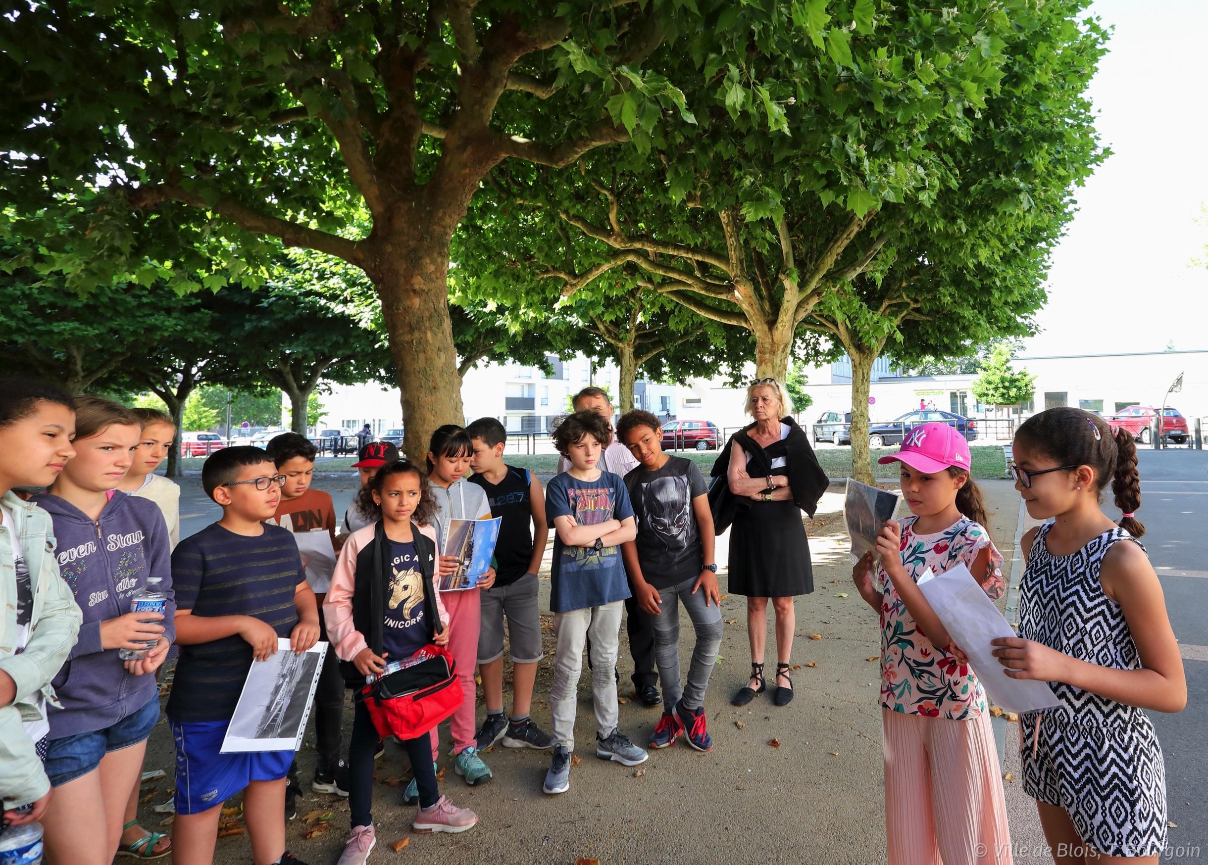 Des enfants rassemblés à l'extérieur écoutent les explications de leurs camarades.