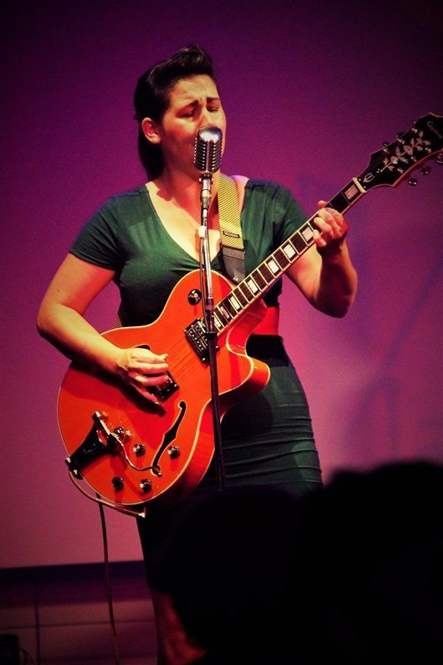 Ady sur scène à la guitare.