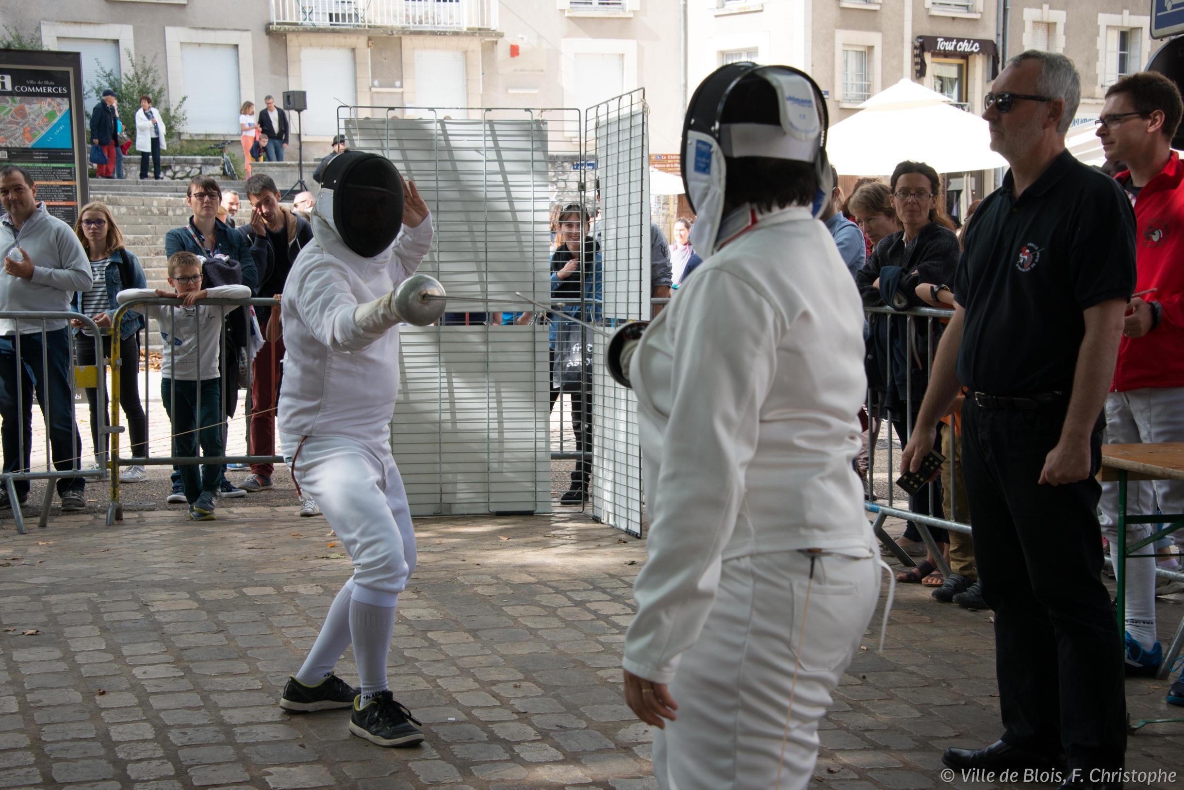 Deux jeunes font de l'escrime dans la rue pendant la fête du Sport.