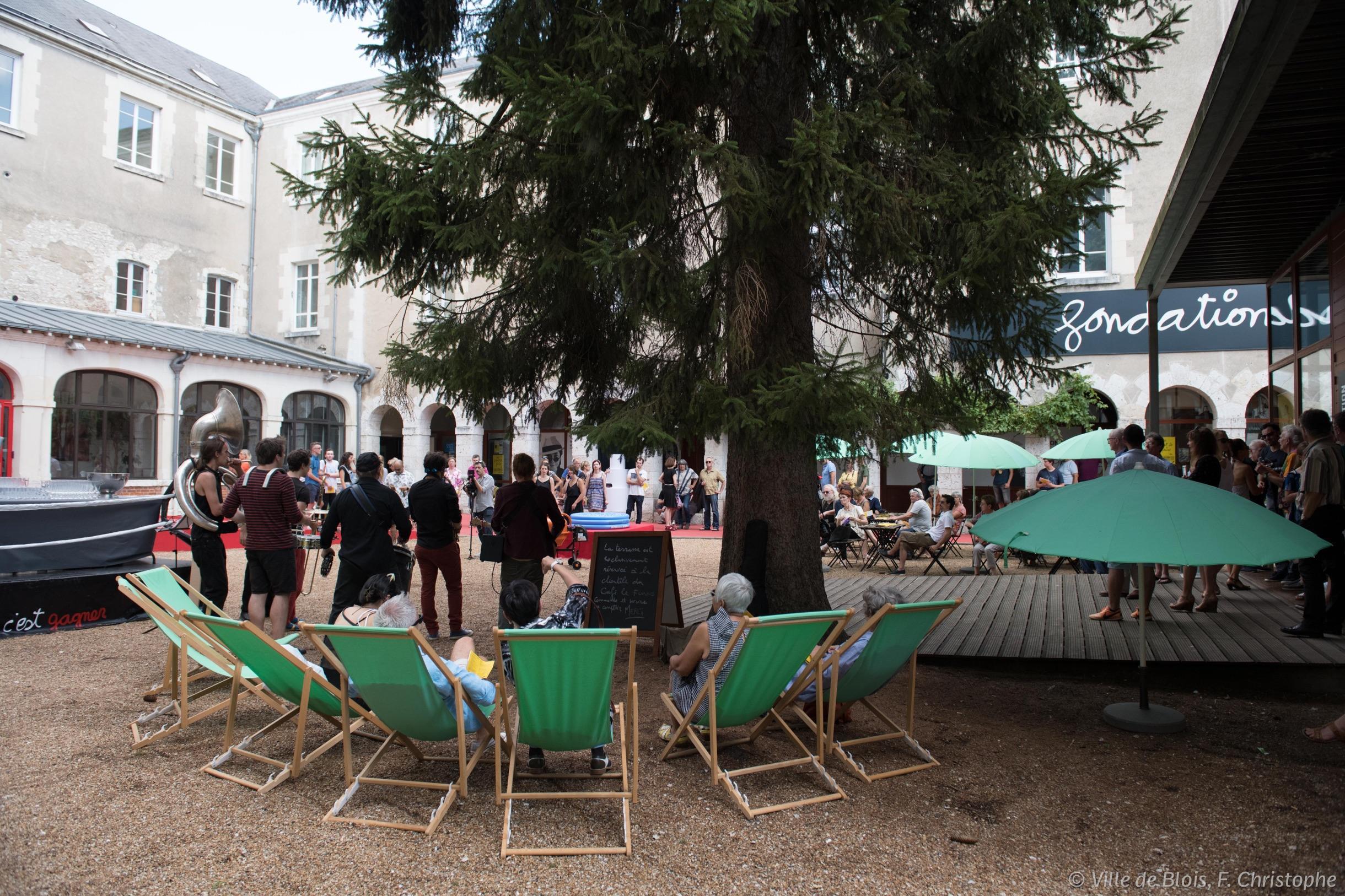 Cour intérieure du cloître dans lequel la Fondation du doute est installée : des transats sont disposés autour d'un arbre qui leur faire de l'ombre.