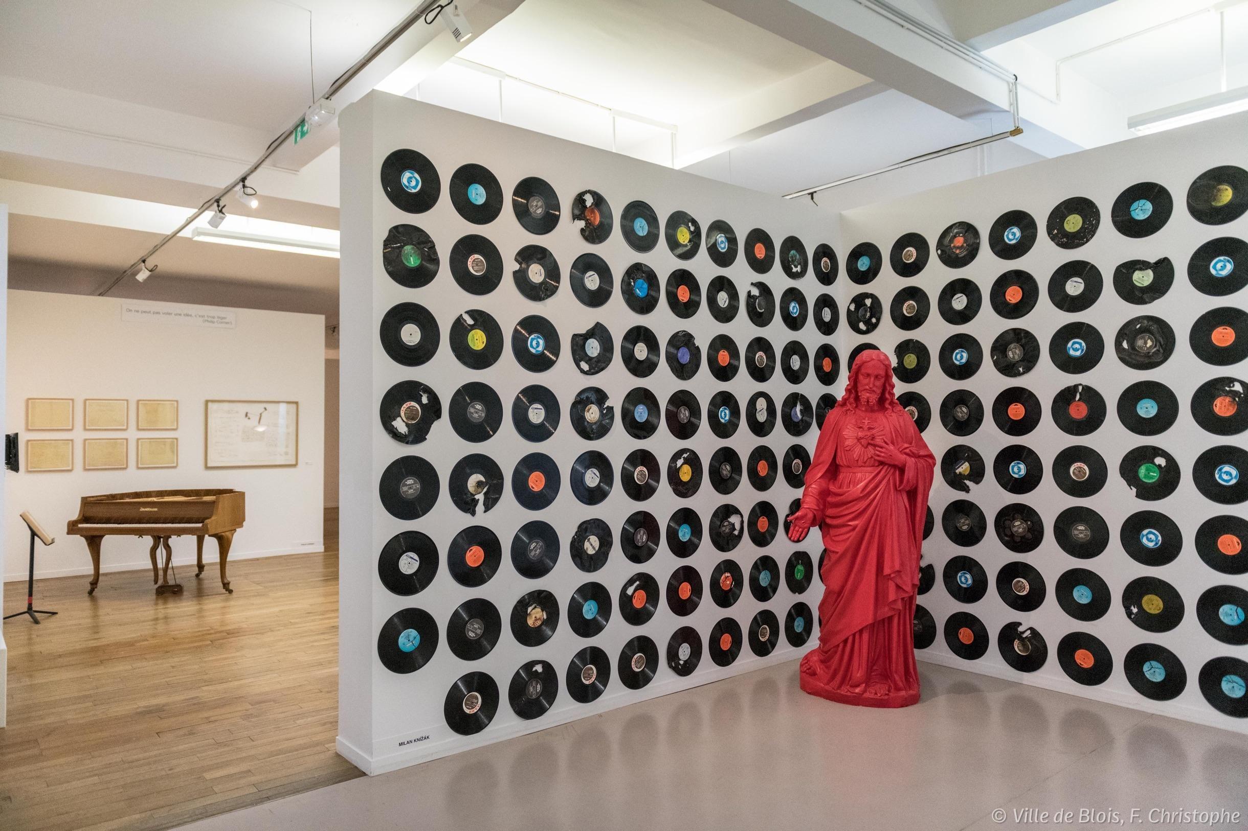 Installation composée d'une sculpture à l'effigie d'un Christ peint en rouge au milieu de disques vinyles 33 tours accrochés au mur.