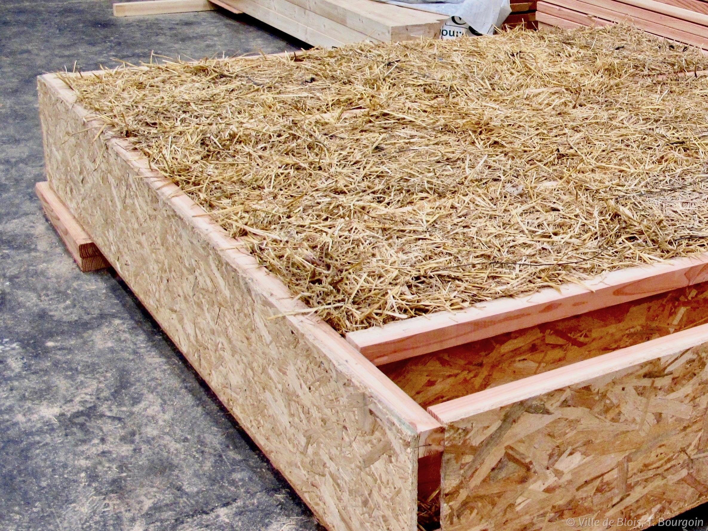 Aperçu du système d'isolation en paille : des caissons en bois sont remplis de paille par les ouvriers.