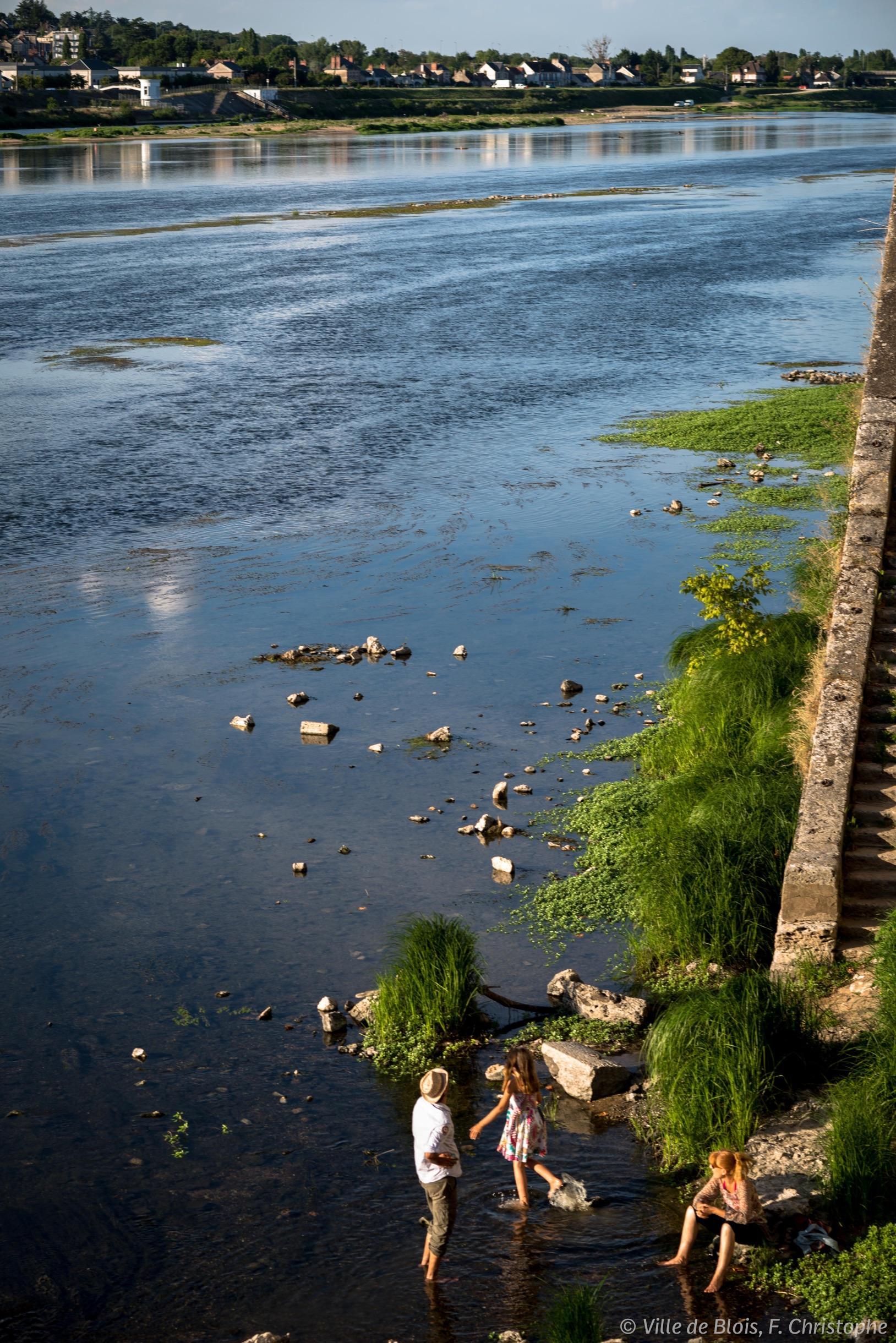 Un groupe de trois personnes font trempette sur le bord de Loire.