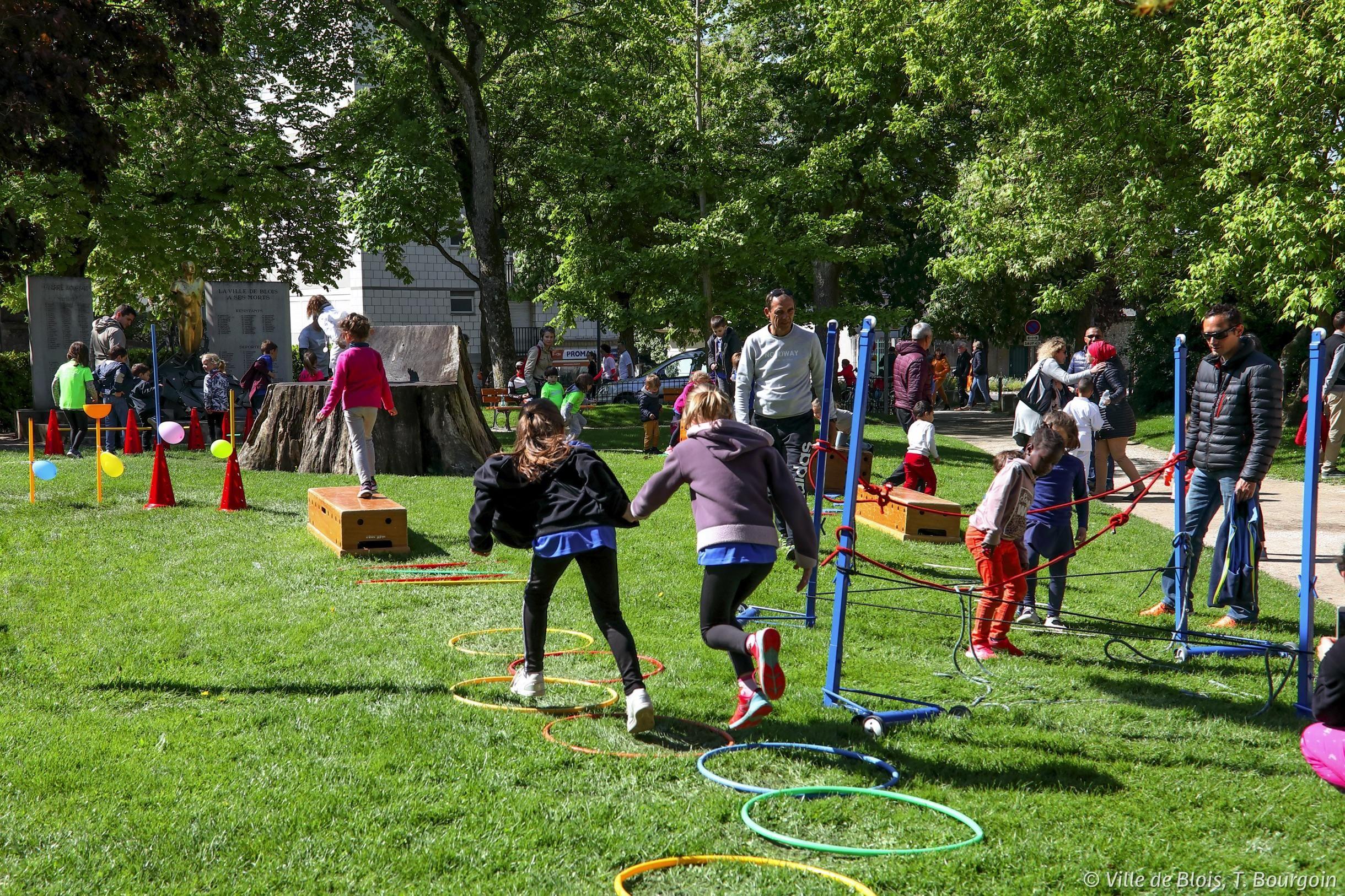 Des enfants sautent dans des cerceaux sur la pelouse de la place de la République.