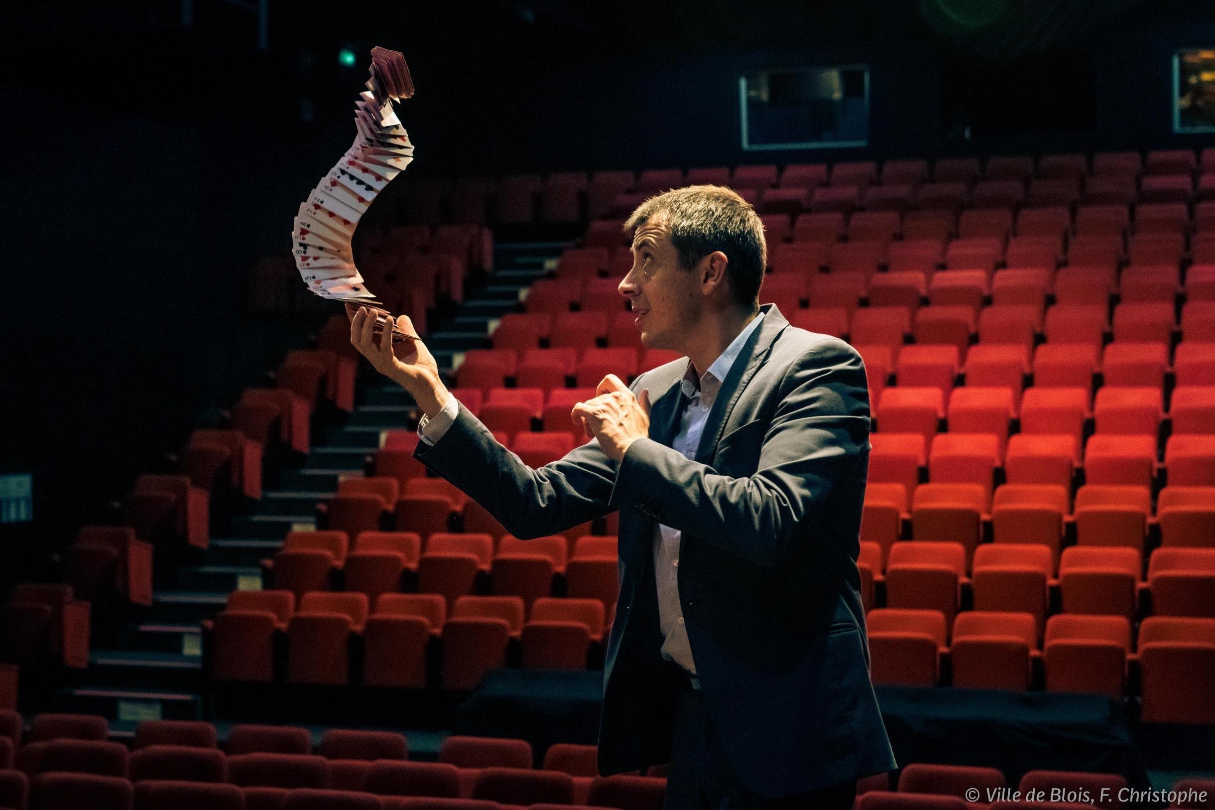 Arnaud Dalaine joue avec des cartes en l'air sur la scène du théâtre Christian-Fechner de la Maison de la magie.