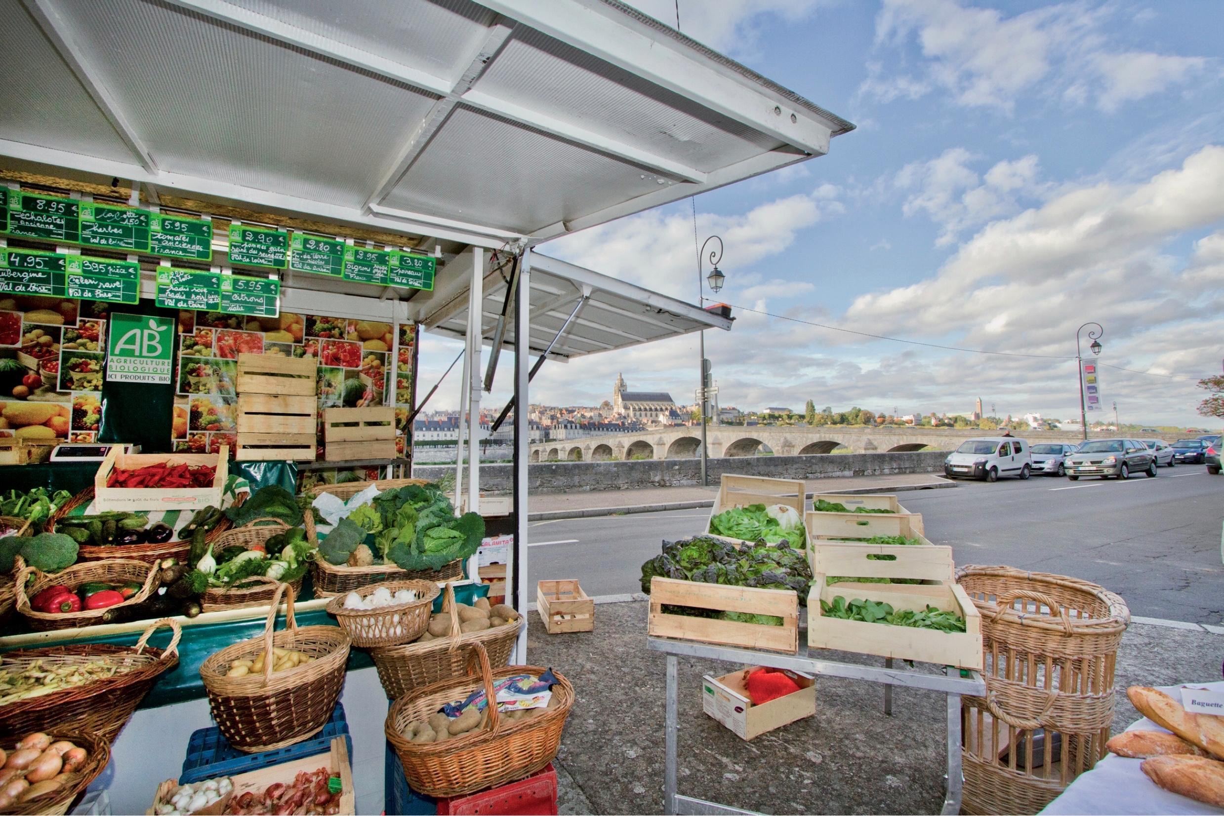 Un des nombreux stands du marché bio présente de nombreux légumes et du pain, avec la Loire et le nord de la Ville en arrière-plan.