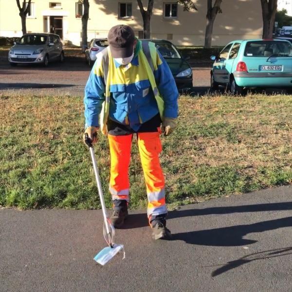 Un agent du service Propreté ramasse un masque usagé jeté sur la voie publique.