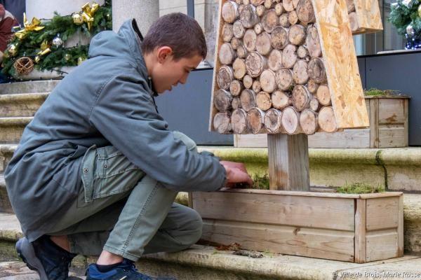 Un apprenti ajuste un sapin conçu en matériaux recyclés.