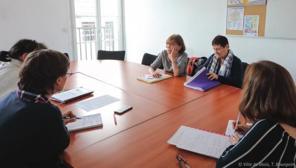 Cinq personnes échangent autour d'une table de réunion.