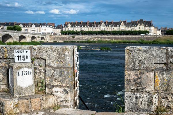 Une borne kilométrique et une échelle limnimétrique sur les quais de Loire.