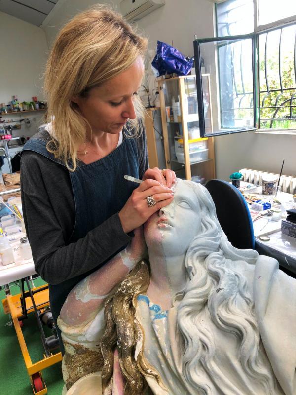 La restauratrice, dans son atelier, travaille sur l'œuvre dont une partie de la polychromie est visible.