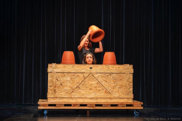 Trois pots retournés et alignés, dont l'un est soulevé par une femme et révèle la tête d'une autre femme.
