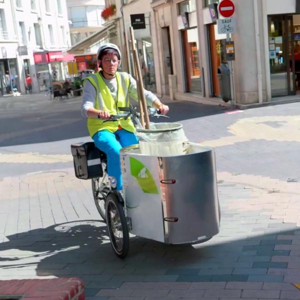 Une agente du service Propreté parcourt les rues blésoises sur un triporteur équipé pour vider les corbeilles à déchets.