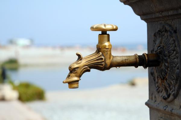 Un robinet fermé, avec un paysage aride en arrière-plan.