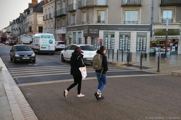 Deux personnes traversent à pied une zone de rencontre.