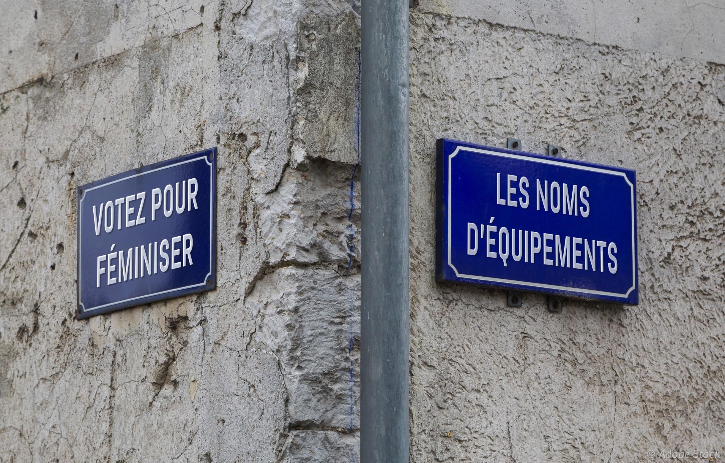 Panneaux de rues à un croisement, renommés «Votez pour féminiser» et «les noms d'équipements».