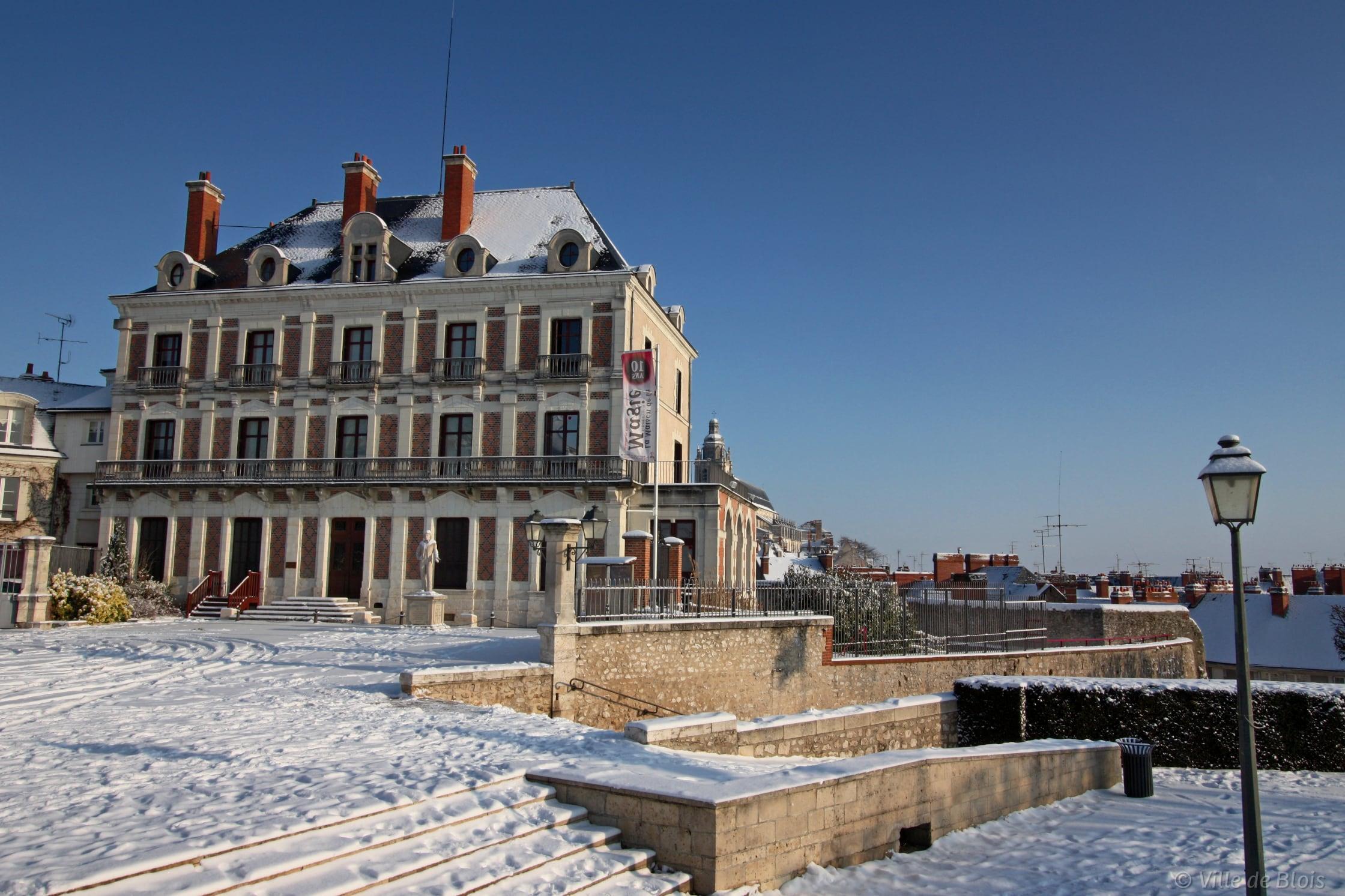 Photo de la façade de la Maison de la magie depuis la place du Château, sous la neige avec un ciel entièrement bleu.