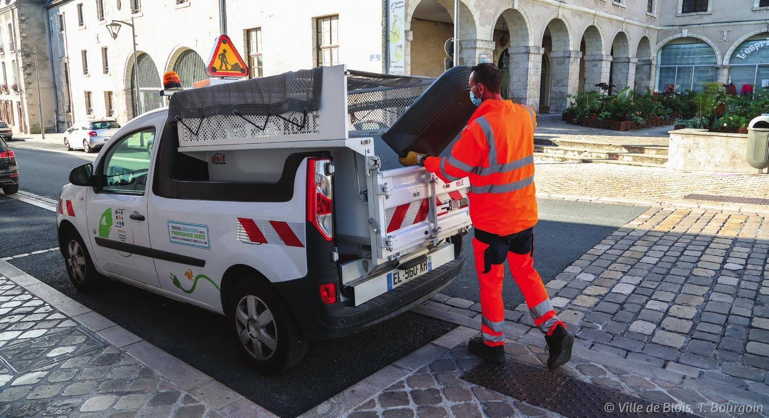 Un agent de la propreté vide une corbeille à déchets dans le bac de son véhicule de collecte.