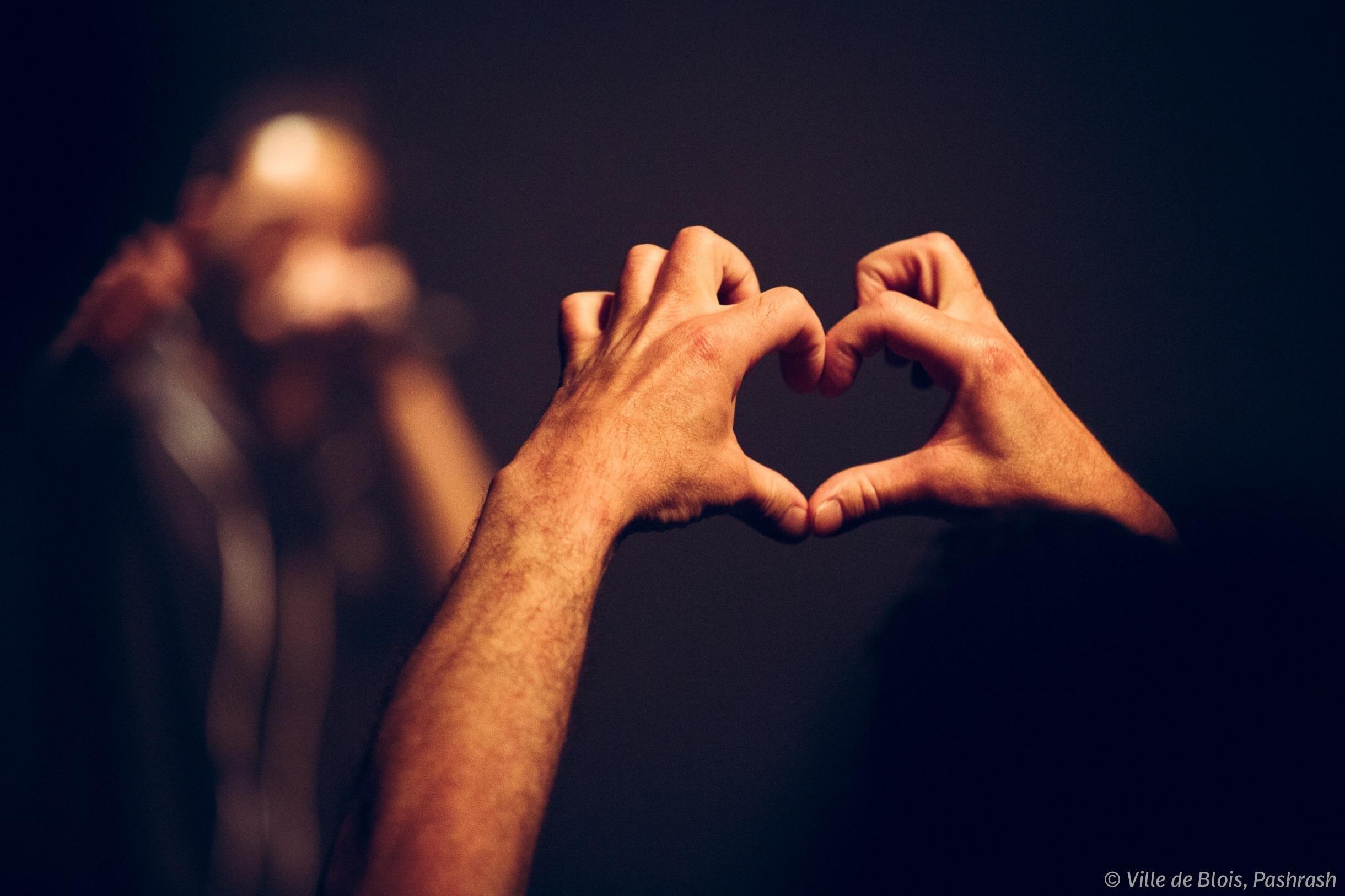 Une personne assistant à un concert forme un cœur avec ses doigts.